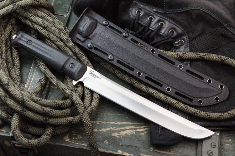 Нож Sensei D2 Satin, КизлярНожи Кизляр<br>Нож Сенсей от Кизляр – особая модель, в которой удалось гармонично объединить русскую практичность с красотой восточных традиций. Кизлярский нож Сенсей имеет клинок из высокоуглеродистой и высокохромистой штамповой стали D2. Она характеризуется максимальной износоустойчивостью, не подвержена абразивным воздействиям и компрессионным нагрузкам. Важная особенность – смещение баланса в сторону клинка, что обеспечивает возможность комфортного использования в любом качестве: резать, рубить и строгать. Высочайшей прочностью нож Sensei D2 Satin от Kizlyar Supreme обязан конструкции full-tang. Особая закалка клинка способствует отличной ударной вязкости и гарантирует надежность при любых нагрузках.<br>