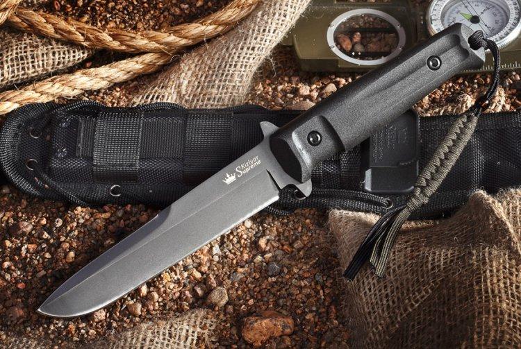 Нож Trident D2, Black TitaniumНожи Кизляр<br>Нож Trident D2, Black Titaniumс двумя упорами, эргономичной рукоятью и многофункциональным креплением Molle обладает превосходной конструкцией. Инструмент выполнен из одной из лучших марок стали. В отличие от других туристических ножей, это изделие позволяет совершать самые разнообразные работы при минимальном риске пораниться. Для этого предусмотрены продолжительные упоры. Толщина клинка около 5 мм придает ножу необходимую массивность во время нанесения колющего удара и обеспечивает его прочность при поперечных нагрузках. Матовое покрытие клинка выполняет антибликовую функцию и защищает нож от повреждений. Чехол в комплекте адаптирован под систему крепления MOLLE. Его можно носить с размещением ножа рукоятью вверх или вниз, вешать на поясе или элементах разгрузочной системы, а также, продев ремешок, можно закреплять на бедре. На ножнах размещены подсумки и для других инструментов, заточки, фонарика и пр. Все эти выраженные конструктивные достоинства обеспечивают изделию повышенную надежность и практичность. Нож Кизляр Тридент с гарантийным талоном поставляется в подарочной упаковке. Он будет великолепным презентом для настоящего мужчины.<br>
