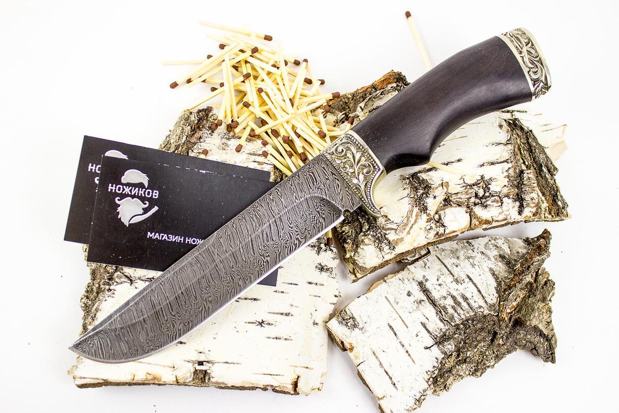 Нож Варяг, дамасская стальКузница Семина<br>Редкая форма ножа «Варяг» с первого взгляда скажет знающему человеку, что он не является оружием. Этот заметный признак - форма лезвия, или так называемая категория «без острия», где угол, под которым сходятся обух и скругленное лезвие, составляет более 70 градусов. У клинка прямой обух, ближняя к острию половина которого являет собой незаточенное фальшлезвие, спуски выполнены по всей длине. Рукоять изготовлена из древесины граба с подпальцевой выемкой и украшена узорчатым мельхиоровым литьем. Уникальные свойства древней дамасской стали создают сдержанную красоту кованого ножа «Варяг», превращая его в престижный подарок. с рукоятью из граба<br>
