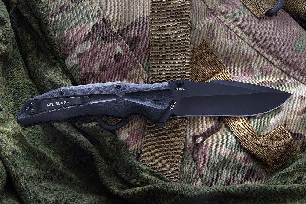 Нож складной НТ-2 (Black), Mr.BladeРаскладные ножи<br>Нож складной HT-2 (Black) от популярного бренда Mr. Blade – инструмент-флиппер: раскрывать его можно как двусторонним шпеньком, так и с помощью «плавника». Нож крупного размера обладает конструкцией осевого узла. Форма клинка создана на основе clip point. Складной туристический нож выполнен из популярной стали D2 с заявленной твердостью 58-60 по Роквеллу. Поверхность обработана полимерным покрытием stonewash. Высокое качество исполнения, а также замок liner lock 2,5 мм толщиной, делают его по-особому надежным. По функциональности раскладной нож для похода и туризма можно считать универсальным. Ведь ему практически нет равных!<br>