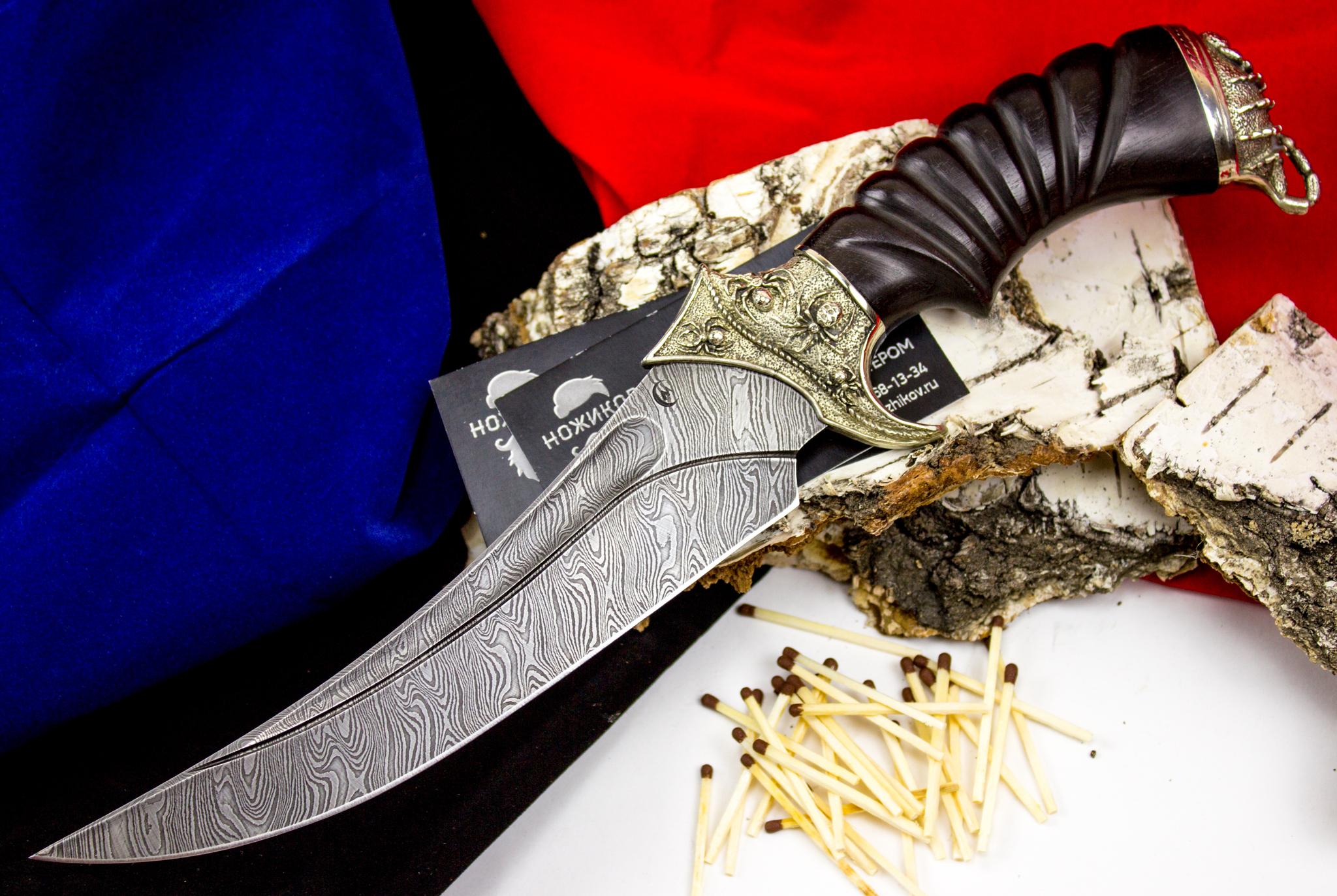 Нож Корсар с резной рукоятью , дамасская стальКузница Семина<br>Отличие этой модели ножа от остальных в серии «Корсар» - оформление. Как и остальные экземпляры клинков, представляющих данную серию, она заставляет вспомнить о море и пиратских саблях. Времена меняются, а ценность качественных режущих инструментов не уменьшается, скорее, даже увеличивается. Редкие старые клинки выдержат столкновение с дамасской сталью, из свойств которой проистекают уникальные характеристики ножа «Корсар» - прочность, гибкость и долго сохраняемая острота. Нож «Корсар» отличается повышенным обухом, и этот параметр исключает его из категории холодного оружия. Рукоять изготовлена из ценных, обработанных влагостойким составом пород дерева, имеется удобная подпальцевая выемка. Материал ограничителя гарды и тыльника – мельхиор, декорированный узорным литьем особой формы.<br>