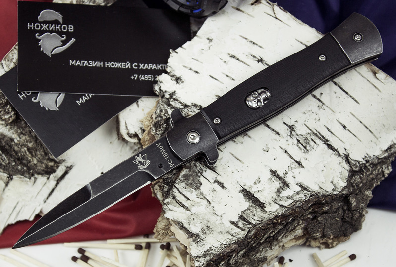 Выкидной нож ПацанВыкидные и автоматические<br>Стильный выкидной нож Пацан понравится серьезным мужчинам, которые обладают повышенной брутальностью. С таким аксессуаром можно легко произвести впечатление на окружающих и показать свой закаленный характер. Выкидной нож с кнопкой относится к стилетам. Такой вид ножей появился достаточно давно и остается популярным по сей день. Относительно компактные размеры и легкий вес делают изделие максимально удобным в процессе транспортировки. Его можно без проблем разместить в кармане штанов или куртки.Внешний вид ножа достаточно строгий и сдержанный. Металлические элементы покрыты черной, матовой краской. В дизайне также поучаствовали накладки из надежного стеклотекстолита. Чтобы придать изделию более брутального вида производитель сделал на нем кнопку в виде черепа. Механизм открывания работает прекрасно и моментально отправляет лезвие в боевую позицию. Нож с черепом — это тот аксессуар, который должен быть у каждого настоящего мужчины.<br>