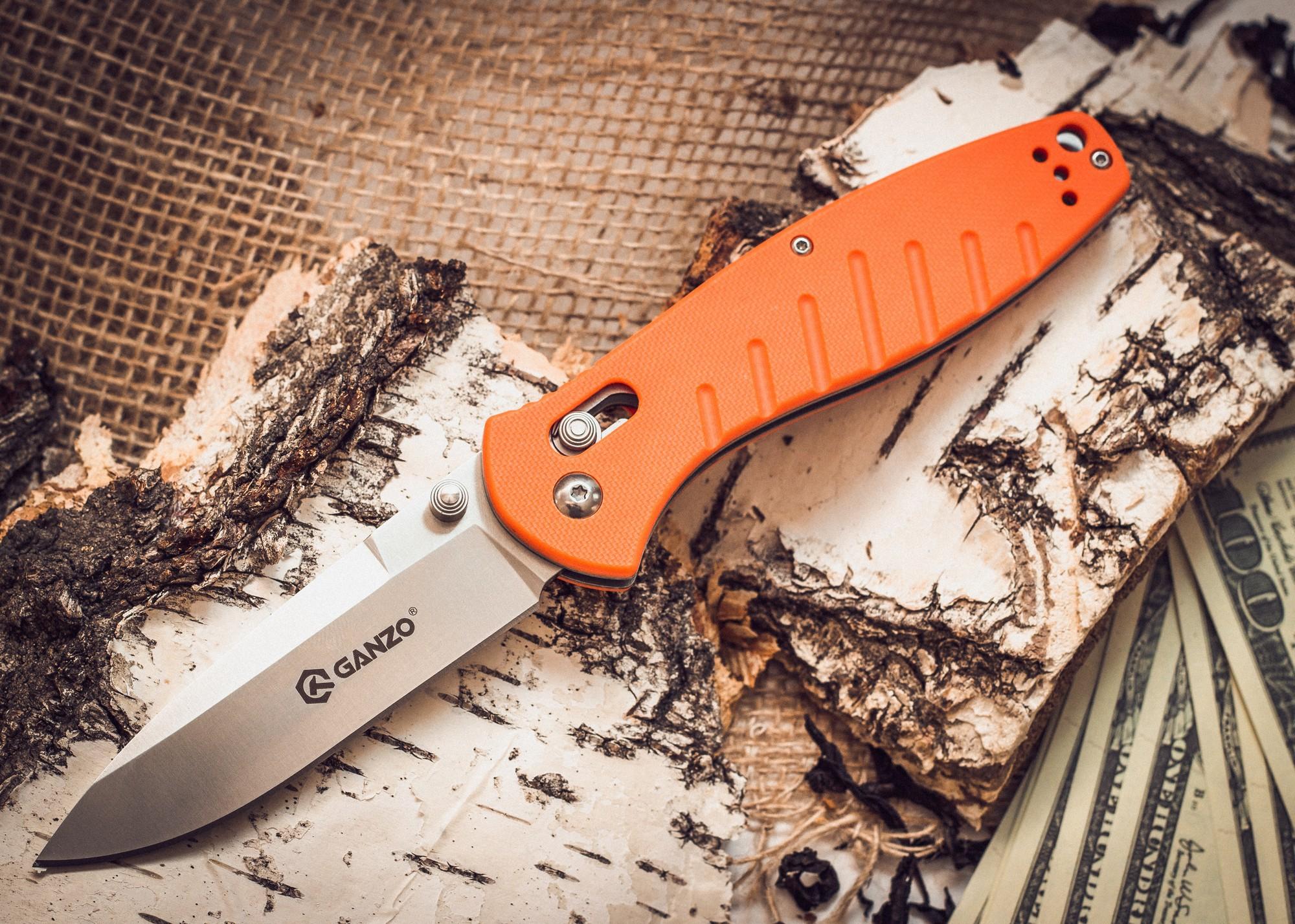 Складной нож Ganzo G738, оранжевыйРаскладные ножи<br>Чтобы выдержать эксплуатацию в таких жестких условиях, какие предполагает отдых на природе, нож должен быть собран из самых качественных комплектующих. Так, клинок Ganzo G738 выпущен из нержавейки, которая нашла широкое применение в этой отрасли. Марка 440С содержит в составе целый ряд легирующих добавок, которые позволяют улучшить ее свойства, повысить стойкость к ржавлению и способность оставаться остро заточенной. Геометрия клинка грамотно продумана. Это drop point с пониженной линией обуха. Острие клинка немного приподнято, за счет чего режущая кромка фактически удлиняется. Заточка ножа ровная и ее легко подновить, используя самую обычную карманную точилку. Что касается габаритов клинка, то это длина 8,9 см, позволяющая легко использовать нож для чистки рыбы, приготовления бутербродов, и толщина 3,3 мм.<br>В каждом из крайних положений (открытый и сложенный нож) лезвие хорошо фиксируется. Этому способствует использование замка Axis-Lock. В нем применяется небольшой металлический штифт, который и определяет положение клинка. Разблокировать такой замок можно даже одной рукой, что является несомненным преимуществом для туристов и охотников.<br>