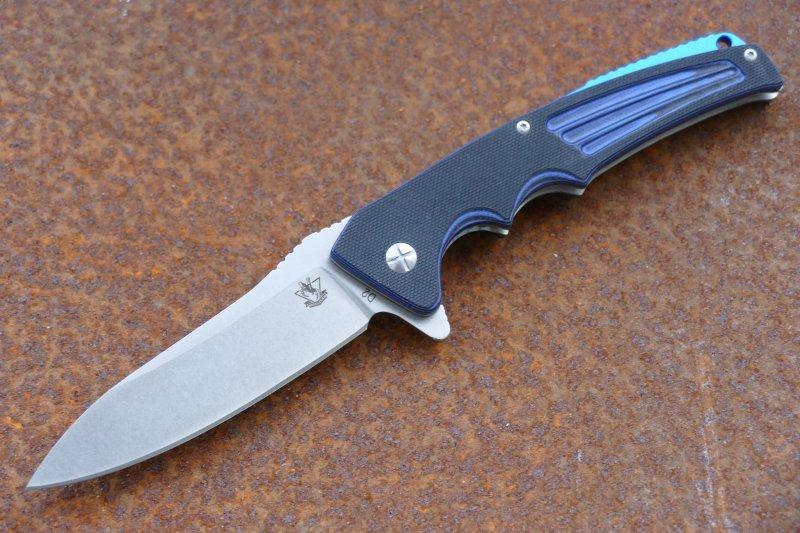 Складной нож ЗадираРаскладные ножи<br>Если вам хочется приобрести крутой и стильный ножик, но жалко денег на «зт» или «себензу», обратите внимание на складной нож Задира. Эта модель подтверждает тот факт, что нож из бюджетного сегмента также может иметь стильный и брутальный вид, а также отличные рабочие характеристики. Рукоять ножа выполнена из двухцветного композитного материала. В местах шлифовки рукояти видны красивые цветовые переходы. Спинка рукояти оснащена вставкой из материала ярко-синего цвета. Клинок имеет классическую геометрию с упором для большого пальца.<br>