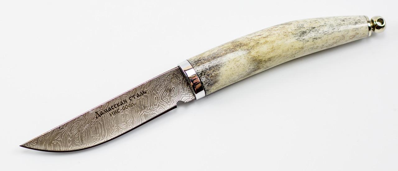 Нож Тигр малютка, дамасская сталь, рог лосяНожи Павлово<br>Ручная работа и оригинальность дизайна, делает нож Тигр малютка, дамасская сталь, рог лося одним из самых достойных изделий подобного рода. Прочные материалы, из которых он изготовлен, позволяют использовать нож в любых климатических и природных условиях. Такой короткий охотничий нож Тигр долго сохраняет свои первичные характеристики, не теряя остроту заточки.В комплекте идут ножны из натуральной кожи, что значительно обезопасит от случайных ранений. Рукоять ножа выполнена из прочных и натуральных материалов, что по достоинству оценят любители эксклюзивных изделий.Данный охотничий нож из дамасской стали может стать отличным подарком, он займет достойное место в коллекции, как охотника, так и простого любителя походов.<br>Общая длина мм: 185Длина клинка мм:85- 90Ширина клинка мм: 22Толщина клинка мм: 3.0Твердость клинка по шкале HRC: 60Тип стали: дамасская стальРукоять: Рог лося, литьё- дюраль, мельхиор.Ножны: Натуральная кожа.Комплектация: : нож, ножны, сертификат<br>