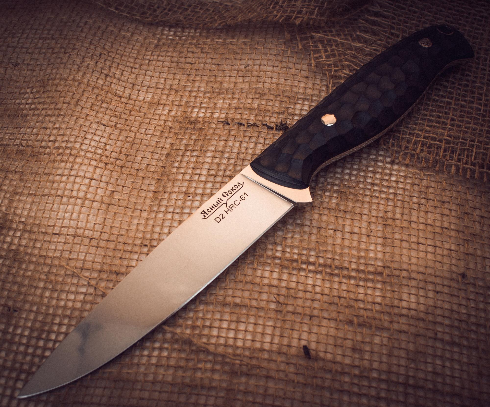 Нож Хищник, стилизация под каменьНожи Павлово<br>Нож Хищник - результат долгой творческой работы. Мы с гордостью можем сказать, что получился популярный нож, который отлично справляется с различными типами задач. Главное его свойство универсальность.За счет формы клинка он хорошо справляется с любым типом продуктов. Именно такого ножа, как правило, всегда не хватает на дружеских пикниках. Нож имеет хорошо контролируемый деликатный рез. Парное мясо, свежие овощи, сыр и колбаса - этому ножу все по плечу. Но при этом он легко настрогает щепок или расколет небольшое полено пополам.Нож имеет удобную ухватистую рукоять, выполненную из надежного ударопрочного материала G10. Этот материал не боится влаги, сырости или резкого изменения температуры. Декоративное рифление, стилизованное под камень, делает этот нож не только полезным, но и стильным элементом экипировки.Ну и конечно, такой нож не может обойтись без удобных ножен. Ножны четко повторяют контуры ножа и обеспечивают его надежную фиксацию. Две петли дают возможность выбрать тот тип подвеса, который удобен именно вам - свободный или фиксированный. Завершающим штрихом, подтверждающим высокое качество ножа, является логотип компании «Ясный Сокол».<br>