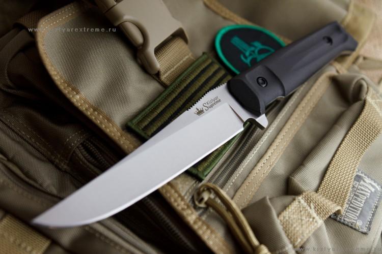 Тактический нож Croc AUS-8 S, КизлярНожи Кизляр<br>Crocполучил свое название от английского слова Croc (Crocodile) из-за сходства его красивого и остро-заточенного клинка с крокодилом.  Клинок ножа Croc ориентирован на высококачественный рез - тонкосведенные слабовогнутые спуски практически от обуха обеспечивают отличные режущие качества. Конструкция лезвия Croc вкупе с высококачественной сталью AUS-8 (57-59 HRC) обеспечивает ножу приятный долгосрочный рез.  Ножи серии Tactical Echelon отличаются формами клинков, но общей для них остается форма рукояти, так как на взгляд дизайнеров Kizlyar Supreme для данной серии она обладает совершенной эргономикой.  Конструкция ножей простая, но максимально прочная: накладки рукояти, изготовленные из Kraton, известного своей износоустойчивостью к истиранию и повышенными фрикционными качествами, прикручены к цельнометаллическому хвостовику резьбовыми стяжками, а также дополнительно проклеены. Стоит отметить, что рукоять идеально совместима с тактическими перчатками.  Безопасность при боевом применении ножа обеспечивает форма рукояти. В роли ограничителя использован выступ на пяте клинка и подпальцевая выемка. Вырезы на подпальцевой выемке продлены на боковую поверхность плашек, образуя в устье рукояти подобие гарды.  Значительную роль играет также сужающаяся к затыльнику коническая форма рукояти, образуя, таким образом, неявный упор. Два выреза на боковых поверхностях накладок, более глубокие у навершия, подчеркивают стремительность форм, а также утоньшают рукоять в поперечной плоскости, улучшая удержание при колющем ударе, создавая тот же самый конический эффект, а также предохраняют рукоять от проворачивания в руке.  Подпальцевая часть рукояти достаточно широкая, и позволяет перехватывать нож ближе к ограничителю, или, наоборот, ближе к навершию, что увеличивает длину рычага при рубящем ударе.  Со стороны навершия есть металлический выступ для нанесения удара. Он имеет скругленную форму и не мешает при работе хватом с упором лад