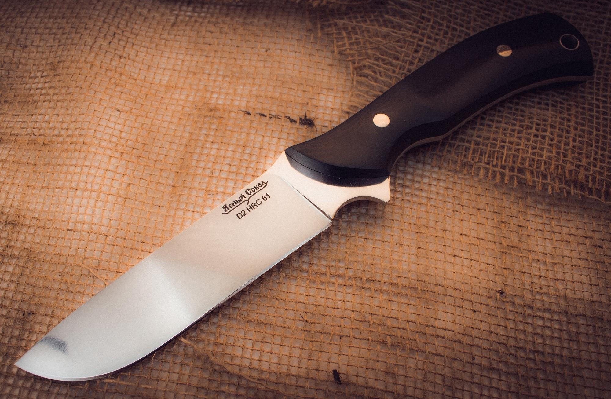 Цельнометаллический нож Охотник-2, сталь D2Ножи Павлово<br>Характеристики:<br><br>Марка стали клинка: D2<br>Длина ножа (мм): 255<br>Длина клинка (мм): 115<br>Длина рукояти (мм): 135<br>Наибольшая ширина клинка (мм): 30<br>Толщина обуха (мм): 3,5<br>Твердость стали: 61 HRC<br>Материал рукояти: G10<br>Материал ножен: кожа<br>Страна изготовитель: Россия<br>Производитель: Ясный Сокол<br><br>Нож Охотник 2 вобрал в себя лучшие наработки по созданию охотничьих ножей. Создавая этот нож, мы исходили из задач, с которыми приходится сталкиваться людям в дикой природе. Каждый элемент этого ножа хорошо продуман и имеет практическое применение. Клинок с широким прямым обухом предназначен для совершения силовых работ. Высокие спуски и тонкая заточка обеспечивают точный и контролируемый рез. Плавный подъем режущей кромки позволяет выполнять разделочные и шкуросъемные работы. Объемная рукоять с выемками для пальцев и упором - обеспечивает уверенный силовой хват. Отверстие в тыльной части предназначено для темляка или подвеса. Рукоять ножа выполнена из стеклотекстолита G10, прочность которого проверена в различных экстремальных ситуациях. Важным дополнением к такому ножу являются удобные ножны из толстой натуральной кожи. Ножны обработаны специальной пропиткой, которая защищает их от влаги и сырости. Две петли позволяют выбрать удобный тип подвеса - свободный или фиксированный. Логотип компании «Ясный Сокол» является стильным штрихом, который завершает композицию.<br>
