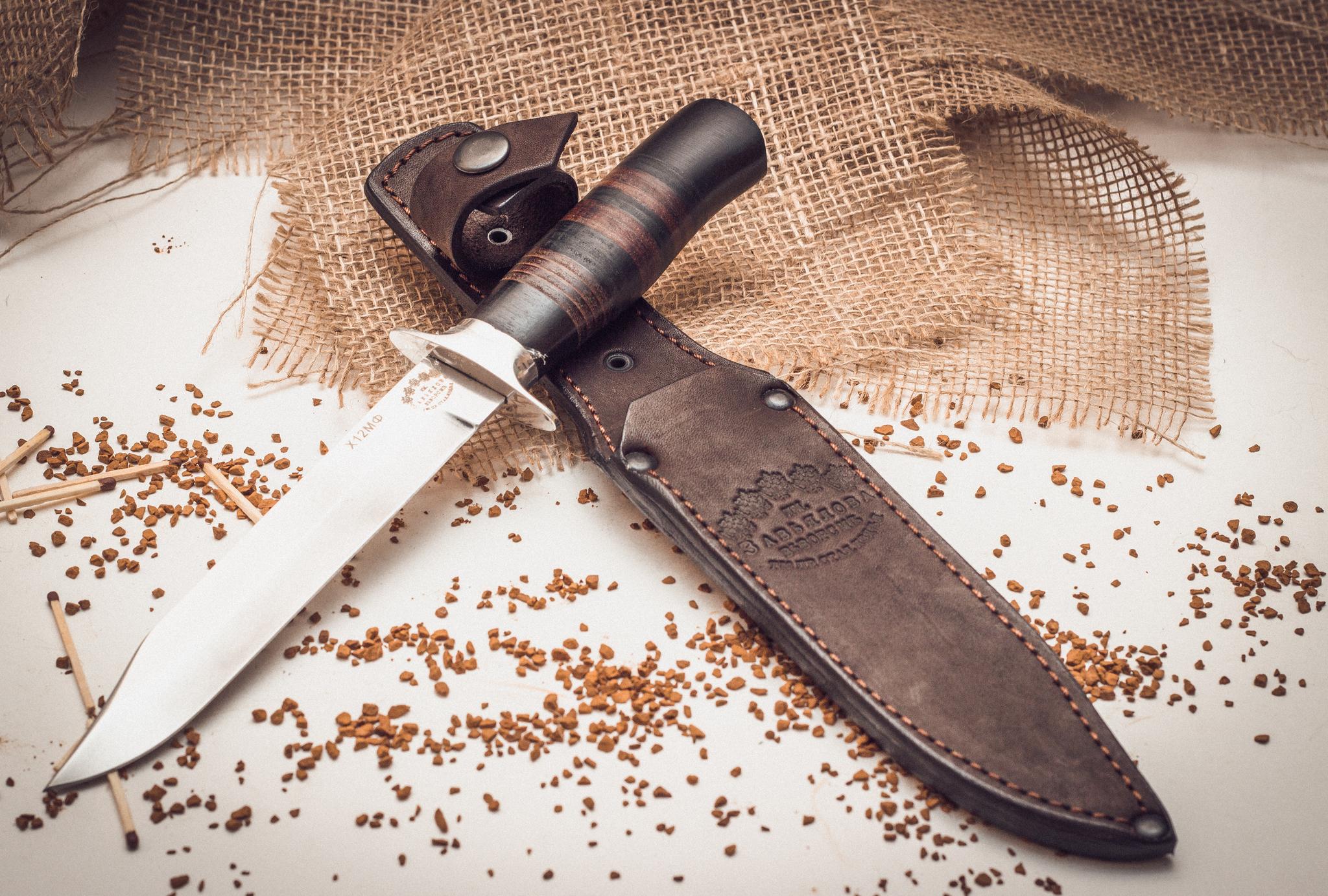 Нож разведчика, Х12МФ, черный граб, кожаНожи разведчика НР, Финки НКВД<br>Для самых опасных экспедиций и отчаянных приключений нужен прочный и надежный нож. Нож, на который можно положиться даже в самой экстремальной ситуации. Нож Разведчика смело можно отнести именно к таким ножам. Во-первых, его клинок изготовлен из кованой стали Х12МФ, что обеспечивает ножу максимальную надежность и прочность. Клинок из этой стали долго остается острым. Во-вторых, нож оснащен развитым упором, который повышает безопасность использования этого ножа. В-третьих, геометрия клинка хорошо приспособлена для реза, уколов и рубки. В качестве дополнительного бонуса, нож укомплектован удобными кожаными ножнами, которые исключают выпадение ножа при активном движении по пересеченной местности.<br>