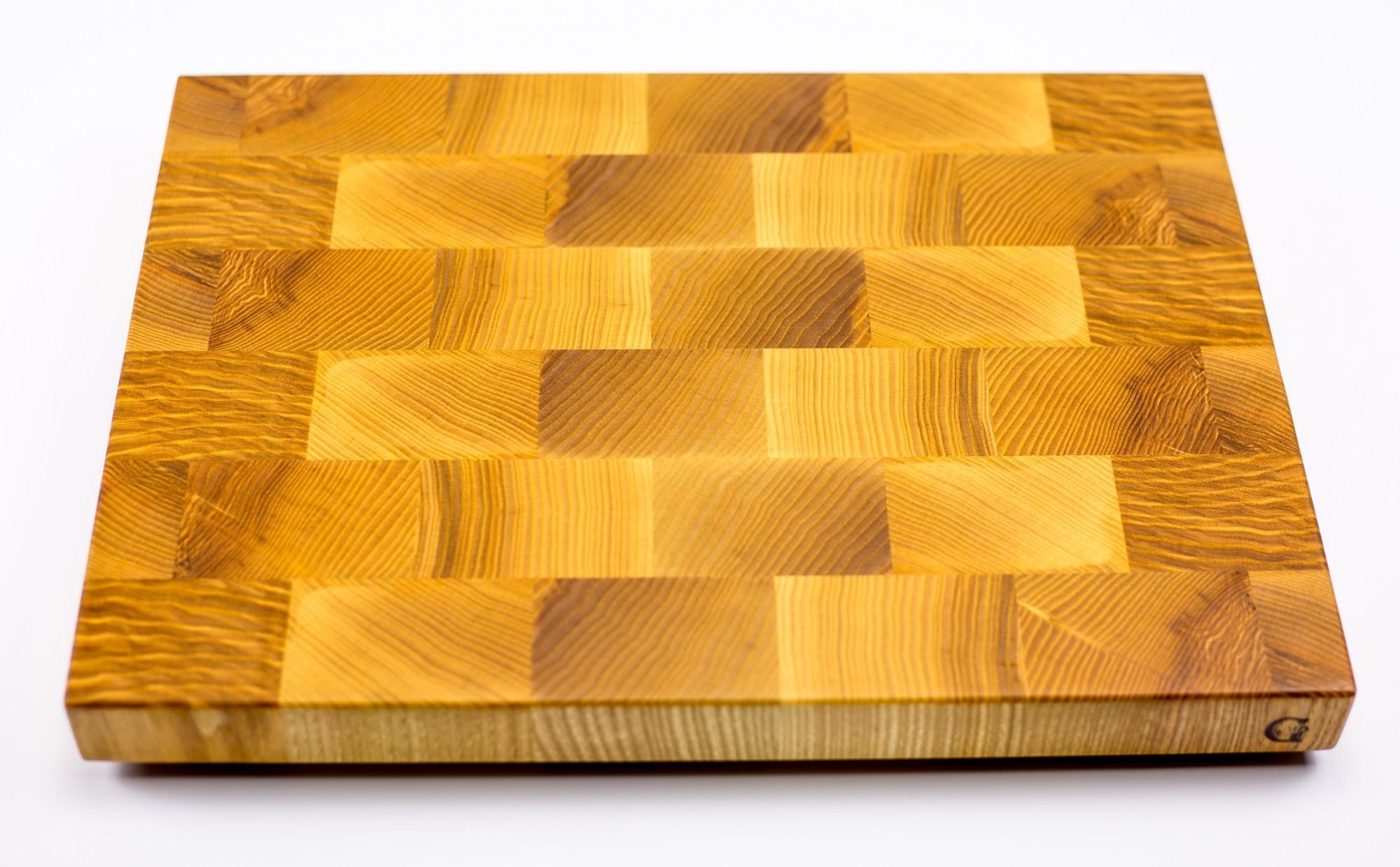 Доска разделочная торцевая, ясень, 27х37х3 смРазделочные доски для кухни<br>Они изготавливаются из лиственных пород древесины, таких как сапеле, дуб, американский орех, ясень, падук, граб, клен, палисандр, венге, груша.<br>Технология их изготовления достаточно сложна. Волокна разделочных досок расположены перпендикулярно плоскости резания. Это позволяет в значительной степени защитить доски от следов ножа, при этом нож намного меньше тупится, что по достоинству смогут оценить коллекционеры ножей.<br>Торцевые разделочные доски склеиваются на водостойкий клей Titebond III Ultimate Wood Glue. Этот клей используется для производства элементов, которые соприкасаются и контактируют с продуктами питания. Все поверхности досок обрабатываются льняным маслом и пчелиным воском для заполнения открытых пор и микротрещин. В зависимости от размера, разделочных досках, для удобства пользования, предусмотрены ручки с боков, канавки для сбора жидкости и опорные ножки. Рекомендации по уходу за разделочными досками<br>Для того, чтобы разделочная доска служила долго и исправно, советуем соблюдать некоторые правила ухода за ней:<br>По окончании работы доску следует вымыть теплой водой и протереть. Нельзя надолго оставлять разделочную доску в мокром виде, или погруженную в воду. Хранить доску необходимо вдали от раковины и плиты.<br>Разделочную доску нельзя сушить в духовом шкафу или микроволновой печи, она должна сохнуть в обычных условиях. Нельзя использовать разделочную доску в качестве крышки для кастрюли или сковороды (от горячего пара доска может лопнуть).<br>Нельзя использовать разделочную доску как подставку под горячее. Нельзя выкладывать на доску горячие, сочащиеся соком, продукты. Разделочную доску для обновления покрытия можно протирать пропиткой (отломить кусочек, растереть по поверхности и оставить на пару часов сохнуть)или льняным маслом (по желанию, или по мере изменения цвета, или раз в месяц).<br>Если вы решили протереть доску маслом, то рекомендуем после этой процедуры 