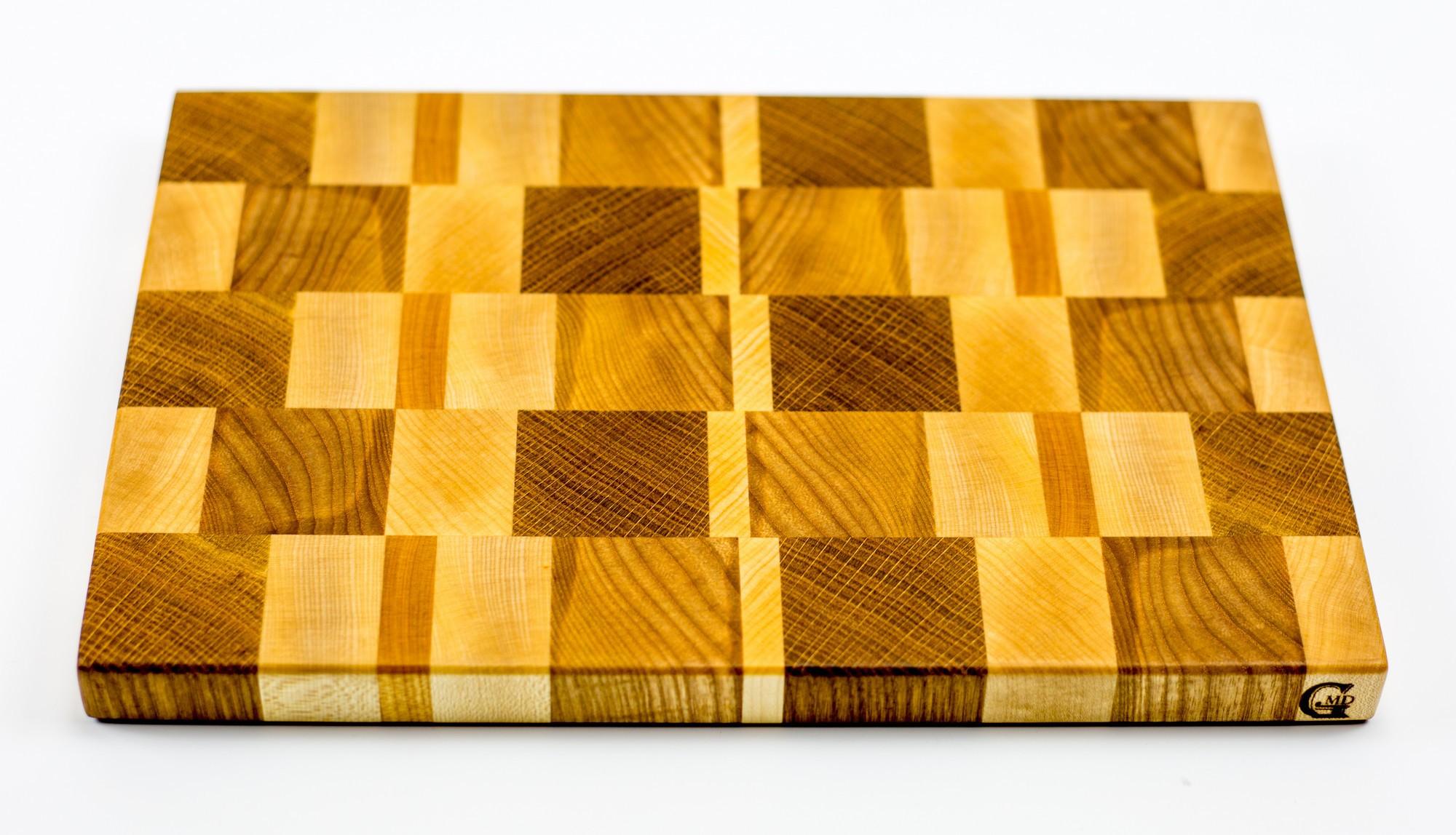 Доска разделочная торцевая, стандартная, 20х30х2 смБренды ножей<br>Они изготавливаются из лиственных пород древесины, таких как сапеле, дуб, американский орех, ясень, падук, граб, клен, палисандр, венге, груша.<br>Технология их изготовления достаточно сложна. Волокна разделочных досок расположены перпендикулярно плоскости резания. Это позволяет в значительной степени защитить доски от следов ножа, при этом нож намного меньше тупится, что по достоинству смогут оценить коллекционеры ножей.<br>Торцевые разделочные доски склеиваются на водостойкий клей Titebond III Ultimate Wood Glue. Этот клей используется для производства элементов, которые соприкасаются и контактируют с продуктами питания. Все поверхности досок обрабатываются льняным маслом и пчелиным воском для заполнения открытых пор и микротрещин. В зависимости от размера, разделочных досках, для удобства пользования, предусмотрены ручки с боков, канавки для сбора жидкости и опорные ножки. Рекомендации по уходу за разделочными досками<br>Для того, чтобы разделочная доска служила долго и исправно, советуем соблюдать некоторые правила ухода за ней:<br>По окончании работы доску следует вымыть теплой водой и протереть. Нельзя надолго оставлять разделочную доску в мокром виде, или погруженную в воду. Хранить доску необходимо вдали от раковины и плиты.<br>Разделочную доску нельзя сушить в духовом шкафу или микроволновой печи, она должна сохнуть в обычных условиях. Нельзя использовать разделочную доску в качестве крышки для кастрюли или сковороды (от горячего пара доска может лопнуть).<br>Нельзя использовать разделочную доску как подставку под горячее. Нельзя выкладывать на доску горячие, сочащиеся соком, продукты. Разделочную доску для обновления покрытия можно протирать пропиткой (отломить кусочек, растереть по поверхности и оставить на пару часов сохнуть)или льняным маслом (по желанию, или по мере изменения цвета, или раз в месяц).<br>Если вы решили протереть доску маслом, то рекомендуем после этой процедуры не пользо