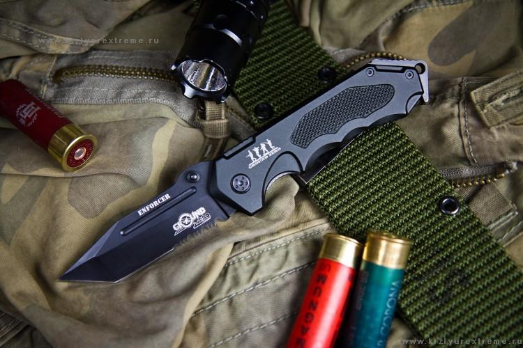 Складной нож Enforcer, 8Cr13MoVРаскладные ножи<br>Обновленный Enforcer – большой и крепкий нож, который так и сияет своей мощью и надежностью. Нож обладает рядом отличных свойств, которые позволяют отнести его к разряду по-настоящему надежных тактических ножей.  Enforcer обладает впечатляющими формами – рифленая эргономичная рукоять и агрессивный клинок в стиле японских коротких мечей танто идеально сочетаются друг с другом и органично работают вместе.  Большие пропорции всех частей ножа, отлично «вливающиеся» в мужскую руку и сравнительно немалый вес дают ощущение сильного боевого оружия. Рукоять ножа повторяет контуры руки и имеет несколько рифленых частей, способствующих надежному хвату, а конструкция обуха клинка позволяет надежно разместить большой палец, обеспечивая, железный хват ножа для колющих ударов и интенсивной работы.  Конструкция рукояти и размещение углублений и рифлений позволяют надежно держать нож практически любым хватом. Выемка под указательный палец плавно образует гарду, защищающую пальцы владельца от соскальзывания на клинок при классическом хвате.  Танто клинок ввиду своего строения идеально подходит для нанесения уколов вперед, а серейтор занимающий треть клинка может быть использован в качестве стропореза и без осложнений резать тросы и ремни, а также легко справляться с мелкими работами по резке твердых предметов.  Ножи Ground Zero имеют острую заточку прямо из коробки. Enforcer превосходно справляется с распространенным тестом заточки ножей - резом стандартного листа А4. Ножи Ground Zero изготавливаются из высококачественных коррозионно-стойких ножевых сталей и проходят специальную термообработку, чтобы улучшить рабочие качества стали и получить, отлично зарекомендовавшую себя, твердость 58 единиц Роквелл. Такая твердость хорошо сохраняет заточку и позволяет в случае необходимости поправить режущую кромку даже в сложных условиях обычным камнем, не прибегая к помощи специального оборудования, которое необходимо для заточки ножей с более в