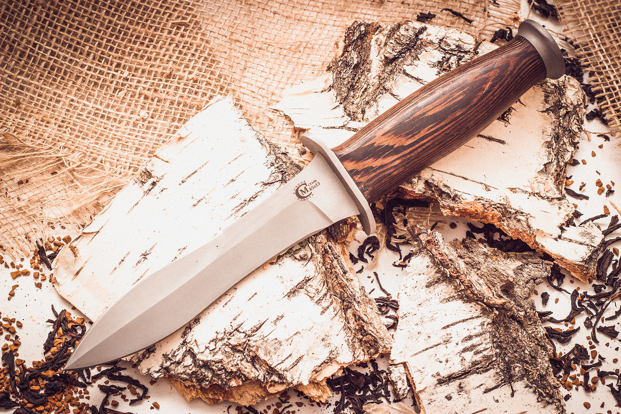 Нож «Ратник», сталь 65х13, венгеНожи разведчика НР, Финки НКВД<br>Классический нож Ратник является отменным оружием ближнего боя. В отличии от прославленного брата образец ножа Ратник от Юрия Семина - это скорее универсальный вариант охотничьего ножа с удобной для хвата рукоятью коричневого цвета и увесистым клинком из нержавеющей стали.В умелых руках он всегда найдет достойное применение. Как и все произведения кузницы Семина, Ратник может похвастаться эксклюзивностью, высоким качеством выполнения и долговечностью.Удачный образец для практичного и желанного подарка как заядлому охотнику или рыбаку, так и коллекционеру оригинальных клинковых изделий!<br>