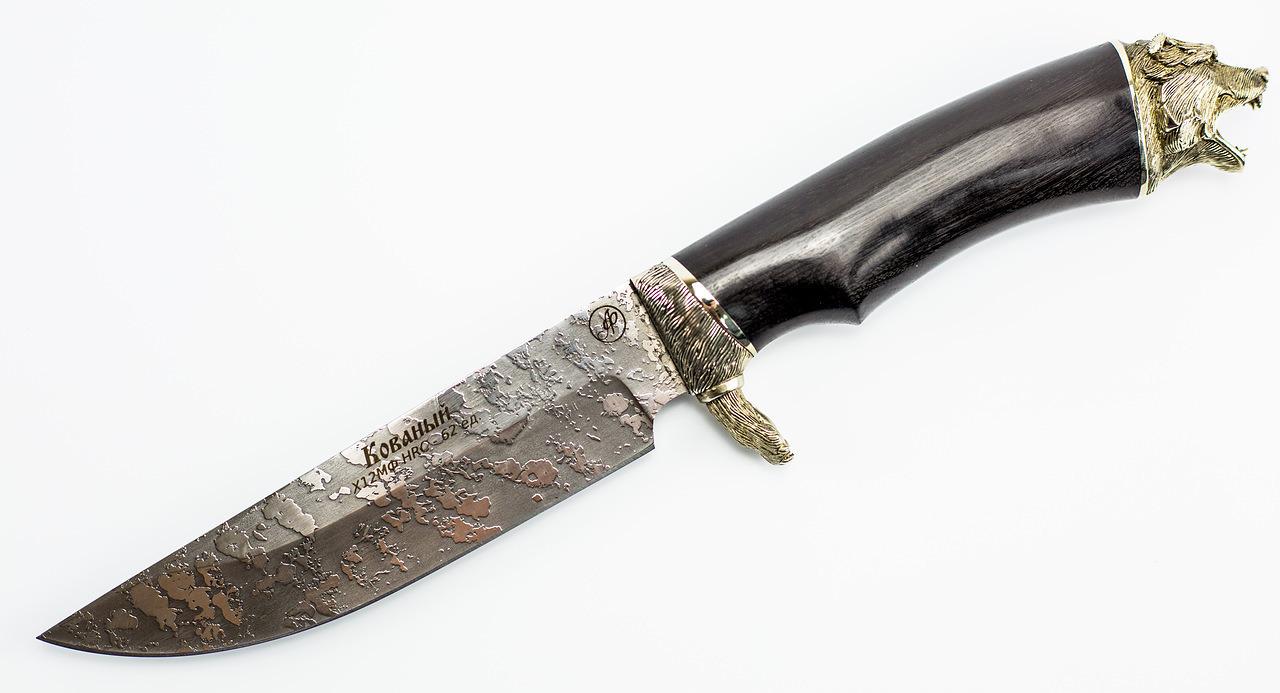 Нож Мишутка с лапой гардой, Х12МФНожи Ворсма<br>Подарочный нож Мишутка производит впечатление на любого, кто берет его в руки. В этой модели сочетаются несколько интересных дизайнерских решений. Клинок ножа выкован из высокотвердой стали Х12МФ и покрыт особым травлением. Рукоять ножа выполнена из натурального дерева с красивым природным узором. Дополнительную красоту этому ножу придают элементы художественного литья, изготовленные из мельхиора. Гарда рукояти выполнена в форме большой медвежьей лапы. На тыльнике рукояти размещено навершие в форме головы медведя, который готов справится с любым соперником. Держа в руках такой нож, обязательно почувствуешь себя сильнее и гораздо увереннее. Если же вам захочется испытать нож в полевых условиях, то для перевозки есть удобный чехол из натуральной кожи.<br>Общая длина мм: 295Длина клинка мм: 150Ширина клинка мм: 36Толщина клинка мм: 2.0-2.4Твердость клинка по шкале HRC: 62Тип стали: Х12МФ ковкаРукоять: Граб, мельхиор.Ножны: Натуральная кожа.<br>
