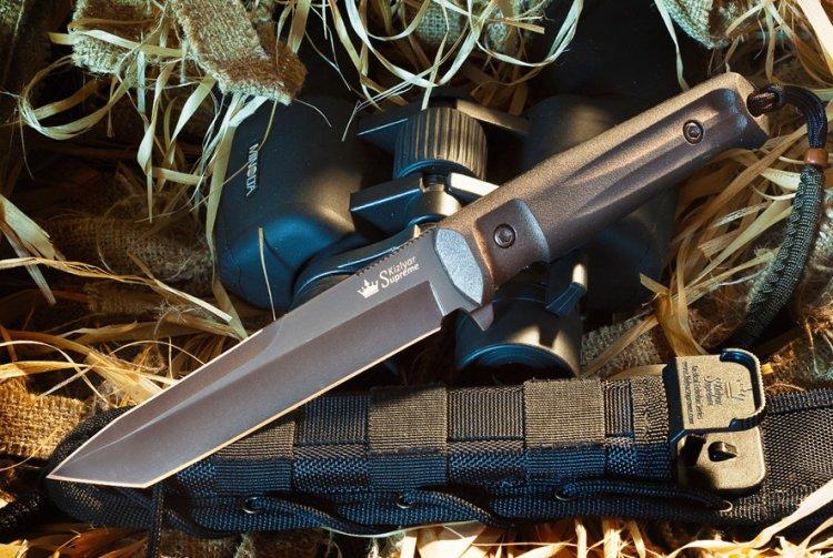 Тактический нож Aggressor D2 Black TitaniumНожи Кизляр<br>Aggressor не относится к холодному оружию, но обладает мощным упором, которым может похвастаться очень ограниченный круг ножей, не относящихся к холодному оружию. Agressror - один из самых ярких представителей новой серии Tactical Echelon, ориентированной на использование в спецподразделениях, а также отлично справляющейся с большинством нужд охотников, спасателей и других групп пользователей, ведь это прежде всего - надежные и функциональные ножи.<br>Ножи серии Tactical Echelon отличаются формами клинков, но общей для них остается форма рукояти, так как на взгляд дизайнеров Kizlyar Supreme для данной серии она обладает совершенной эргономикой. Конструкция ножей простая, но максимально прочная: накладки рукояти, изготовленные из Kraton, известного своей износоустойчивостью к истиранию и повышенными фрикционными качествами, прикручены к цельнометаллическому хвостовику резьбовыми стяжками, а также дополнительно проклеены.<br>Комплектация Нож, чехол с многофункциональным креплением Molle, темляк, международный гарантийный талон, подарочная упаковка<br>