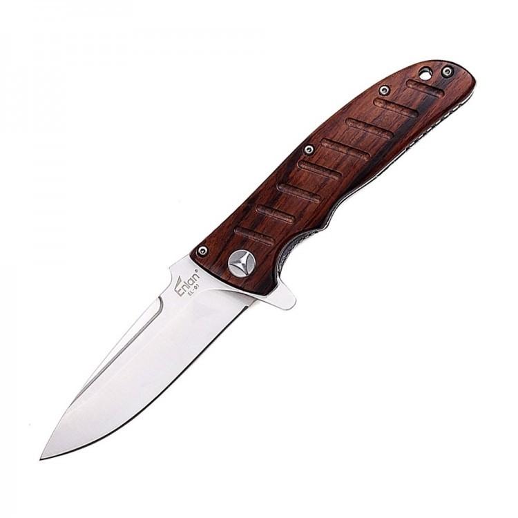 Нож Enlan EL-01Раскладные ножи<br>Enlan EL-01 станет отличным помощником для любителей активного отдыха в условиях дикой природы. Представленный нож благодаря высокой надежности, отменному качеству исполнения, эргономичным формам и продуманному дизайну идеально подойдёт для выполнения самых разнообразных задач.<br>В походных условиях нож является просто незаменимым инструментом, именно поэтому, важно выбрать не только надежную, а и действительно удобную модель, которая будет отлично лежать в руке, как, например, Enlan EL-01. Представленный нож, за счёт эргономичных форм, продуманной конструкции и качественной обработке, отлично лежит в руке и его действительно удобно держать практически любым хватом.<br>Клинок ножа выполнен из закаленной нержавеющей стали марки 8Cr13Mov, благодаря чему он отличается хорошим уровнем прочности и долговечности. Следует отметить, что режущая кромка ножа Enlan EL-01 довольно долго держит заточку и может быть с легкостью переточена в полевых условиях, что позитивно сказывается на простоте эксплуатации, делая нож пригодным даже для самых длительных путешествий.<br>Лайнеры (основа рукояти), также выполнены из нержавеющей стали и имеют специальные прорези, которые значительно облегчают вес конструкции без потери прочности.<br>Накладки же выполнены из дерева и имеют множественные небольшие углубления, которые играют не только декоративную функцию, а и позволяют более уверенно удерживать нож в руках.<br>Особенностью ножа Enlan EL-01, как и любого другого «флиппера», является то, что в открытом положении так называемый «плавник» играет роль своеобразной гарды, дополнительно защищая пальцы от случайного соскальзывания на лезвие ножа во время работы.<br>