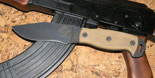 Нож с фиксированным клинком Ontario NS-4 Tan Canvas MicartaOntario Knife Company<br>Нож NS-4 Tan Canvas Micarta, сталь 5160, клинок черный, рукоять с отверстием (микарта), чехол черный нейлон с внутренним пластиком.<br>