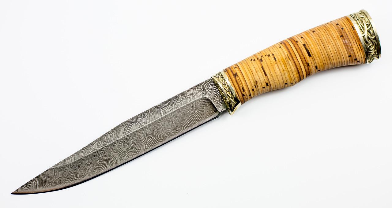 Нож из дамасской стали «Анчар» - рукоять из бересты и мельхиораНожи Ворсма<br>Сталь ДамасскаяРукоять Береста + МельхиорОбщая длина, мм 280Длина клинка, мм 160Ширина клинка, мм 25Толщина клинка, мм 4,1Длина рукояти, мм 120Толщина рукояти, мм 23,7Твёрдость клинка, HRC 61<br>Ножи серии «Анчар» обладают отличительной чертой - большой длиной клинка. Однако 160 мм, превышающие нормируемую длину оружейного лезвия на 10 мм, не дают права называть его оружием. Препятствие тому - форма рукояти без упора-ограничителя. Клинок изготовлен из дамасской стали - прочный, стойкий к изгибу и износу. По форме лезвия, близкой к классической, с прямым обухом и небольшим снижением от середины к острию этот клинок можно отнести к категории универсальных ножей. Рукоять ножа изготовлена из бересты, с неярко выраженной выемкой под пальцы слегка вогнутой формы, имеет ограничитель, гарду и тыльник из мельхиора.<br>