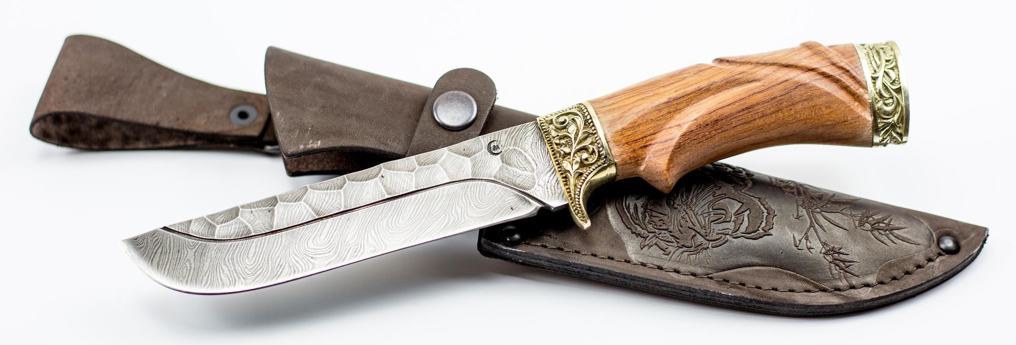Нож Варяг с резной рукоятью , дамасская сталь , литье  скорпионНожи Ворсма<br>Необычная форма ножа «Варяг» привлекает внимание. С первого взгляда становится понятно, что данный нож не является оружием. Это сразу заметно по клинку «без острия», у которого угол между обухом и скругленным лезвием составляет более 70 градусов. Лезвие ножа «Варяг» - с прямым обухом, ближняя к острию половина обуха - фальшлезвие без заточки, спуски выполнены по всей длине. Резная рукоять ножа «Скорпион» изготовлена из древесины ценных пород с подпальцевой выемкой. Гарда с двойным ограничителем и тыльник украшены узорным литьем из мельхиора. Уникальная по свойствам дамасская сталь - основа сдержанной красоты кованого ножа «Варяг».<br>