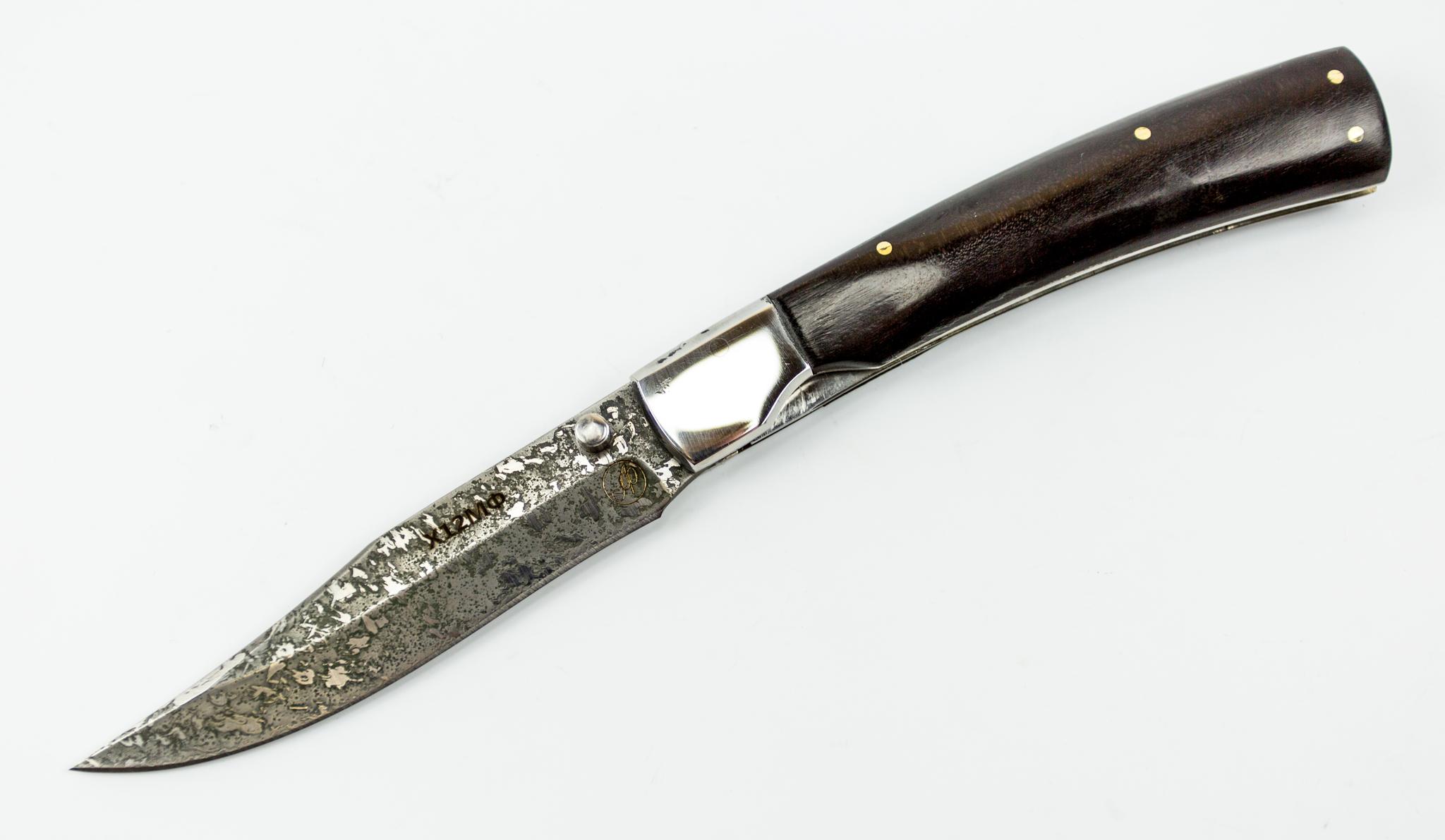 Складной нож Рысь-1, Х12МФРаскладные ножи<br>Складной нож Рысь-1 понравится тому, кто соскучился по настоящим мужским вещицам. Эта модель выполнена полностью ручным способом. Клинок ножа изготовлен из кованой стали Х12МФ, которая по своей твердости сопоставима с литым булатом. Клинок покрыт травлением, благодаря чему приобрел стильный и необычный узор. Узор на клинке отлично сочетается с накладками из натуральной древесины. В комплекте с ножом идет удобный кожаный чехол для ношения на поясе. Среди прочих удобств стоит отметить шпенек для моментального открывания одной рукой. Чтобы ни случилось, вы всегда сможете быстро достать и открыть свой нож.<br>Общая длина мм: 220Длина клинка мм: 98Ширина клинка мм: 20Толщина клинка мм: 2.0- 2.4Твердость клинка по шкале HRC: 61-62Тип стали: сталь Х12МФРукоять: Чёрный грабНожны: Натуральная кожа.Комплектация: нож, ножны, сертификат.<br>Смотреть все складные ножи.<br>