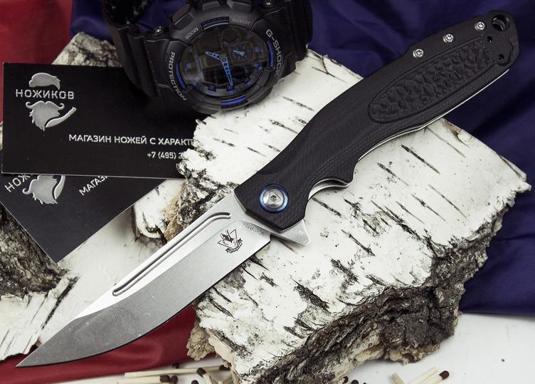 Складной нож Джин, черныйРаскладные ножи<br>Туристический нож Джин сочетает в себе несколько интересных особенностей. Клинок ножа имеет прямой обух, который заканчивается острым кончиком. Нож хорошо приспособлен для выполнения колющих движений. Спуски скандинавского типа начинаются примерно от середины клинка. Такая геометрия обеспечивает ножу острый и деликатный рез, а владельцу помогает легко удерживать нужный угол при заточке ножа. На голоменях клинка расположены фрезерованные долы, который повышаются прочность ножа. Съемная клипса может быть установлена в двух положениях.<br>
